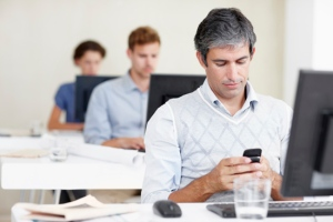Shot of an office worker sending a text message while sitting at his workstation with coworkers behind him